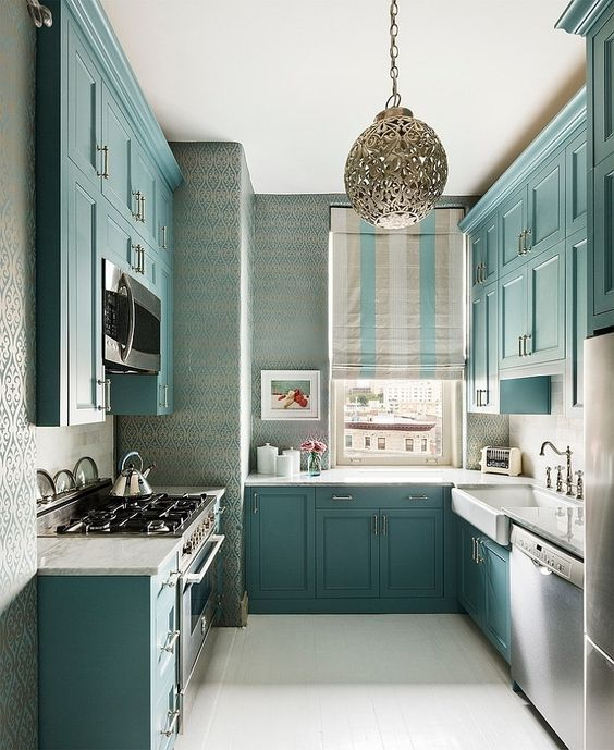 una bella cucina turchese con ripiani bianchi, una finestra invece di un alzatina e rubinetti vintage