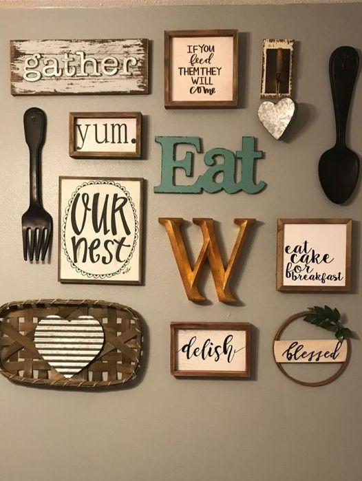 una bella galleria a parete della cucina con lettere e monogrammi, segni in cornici, graziose posate e una piccola ghirlanda con vegetazione