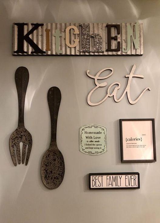 decorazione della parete della cucina con un'insegna in metallo, un'insegna EAT, alcuni grandi pezzi di posate e mini segni vintage sul muro