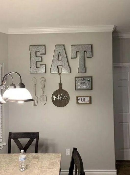 la decorazione della parete della cucina rustica con lettere in metallo, posate in legno, un segno GATHER, un metallo e un cartello incorniciato è adorabile