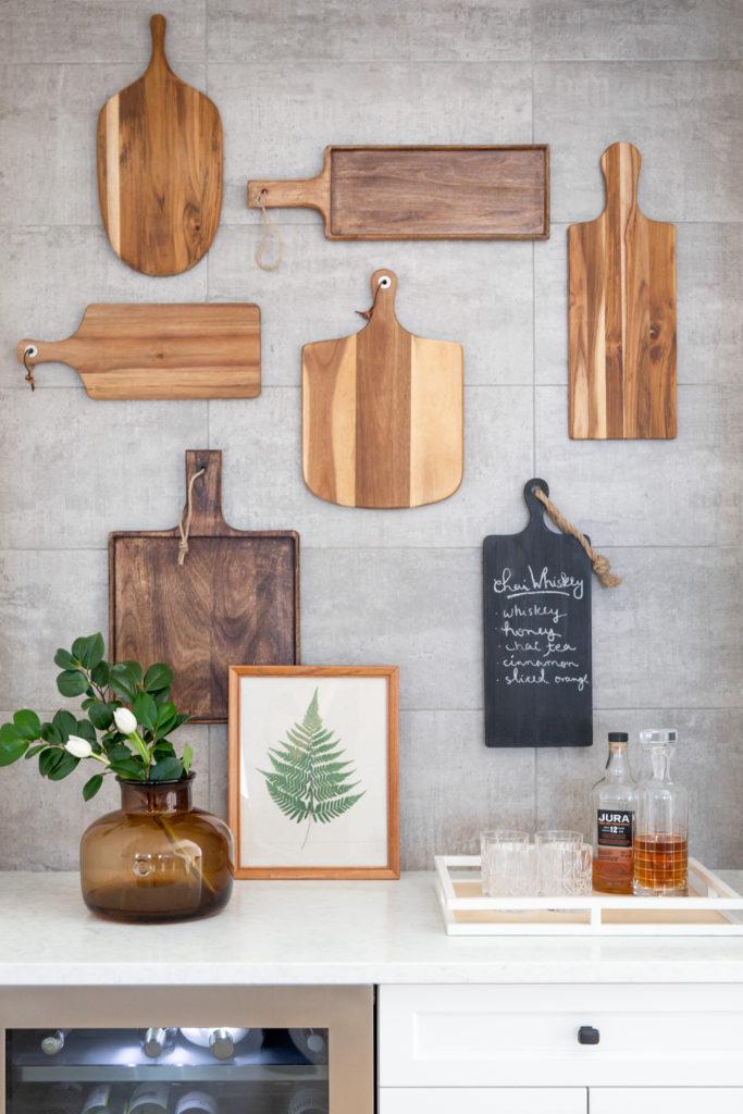 La decorazione della parete della cucina rustica fatta con taglieri disadattati e una lavagna è sorprendente per qualsiasi cucina