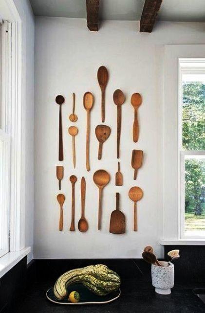 La semplice decorazione della parete della cucina rustica fatta con cucchiai di legno di varie dimensioni e aspetto è un'idea bella e fresca per ravvivare lo spazio