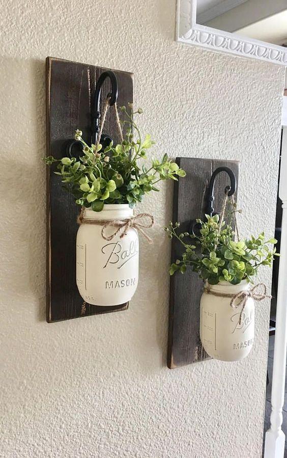 placche in legno tinto scuro con ganci e vasi di muratore imbiancati con vegetazione per decorare le pareti della fattoria