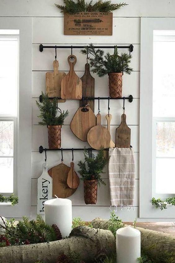 La decorazione della parete della cucina rustica con ringhiere, taglieri, piante in vaso e un asciugamano è un'idea chic e naturale