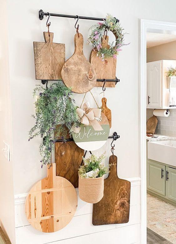 la decorazione della parete della cucina rustica con ringhiere, taglieri, vegetazione, in vaso e in una ghirlanda è un'idea adorabile e facile da realizzare