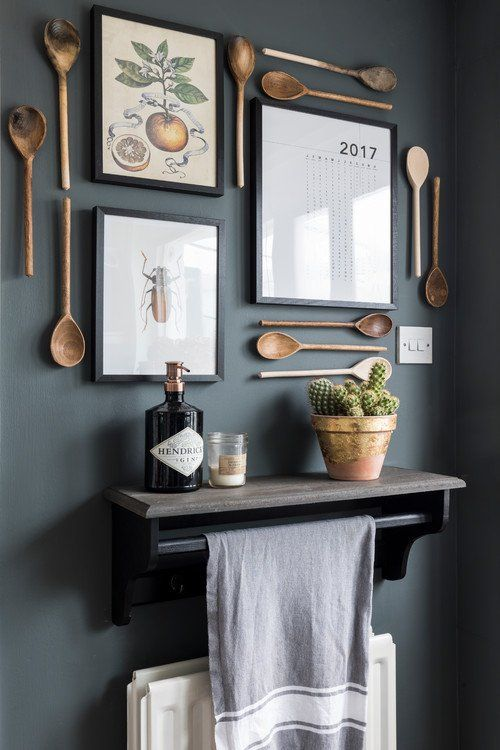 bella decorazione della parete della cucina con posate in legno, poster vintage e un calendario, un cactus in vaso e una candela