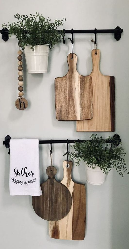 bella decorazione della parete della cucina della fattoria con ringhiere Fintorp, con taglieri, piante in vaso e perline di legno per uno spazio rustico