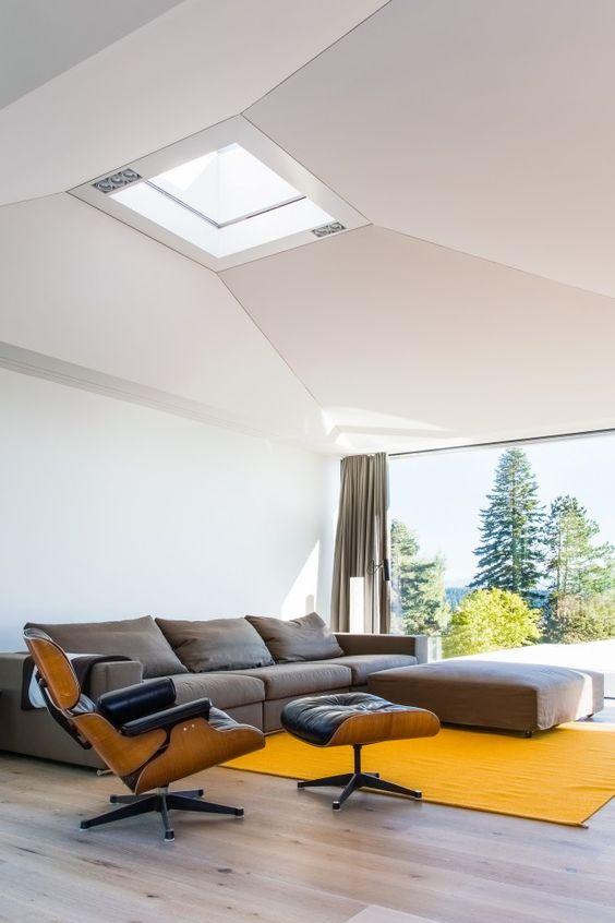 un luminoso soggiorno contemporaneo con un divano basso grigio, un tappeto giallo, una sedia in pelle nera con poggiapiedi e una splendida vista attraverso il muro