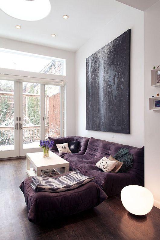 un audace soggiorno moderno con un divano viola basso e un grande pouf, un tavolo bianco e un'opera d'arte nera di grandi dimensioni