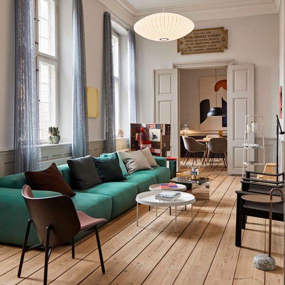 un soggiorno accattivante con un divano basso color smeraldo, tavoli rotondi, varie sedie, lampade e opere d'arte è chic