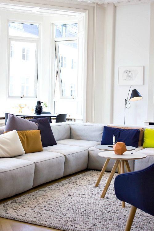 un luminoso soggiorno moderno con un divano basso grigio, una sedia blu audace, cuscini colorati, alcune lampade e tavoli rotondi