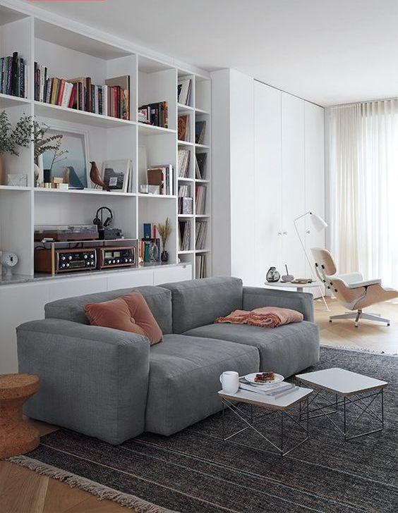 un soggiorno contemporaneo con contenitori incorporati, un divano basso grigio, un paio di tavolini da caffè e un lettino bianco