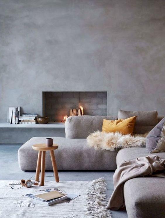 un bel soggiorno minimalista con pareti di cemento, un camino incorporato, un divano grigio basso, uno sgabello roudn e vari tessuti