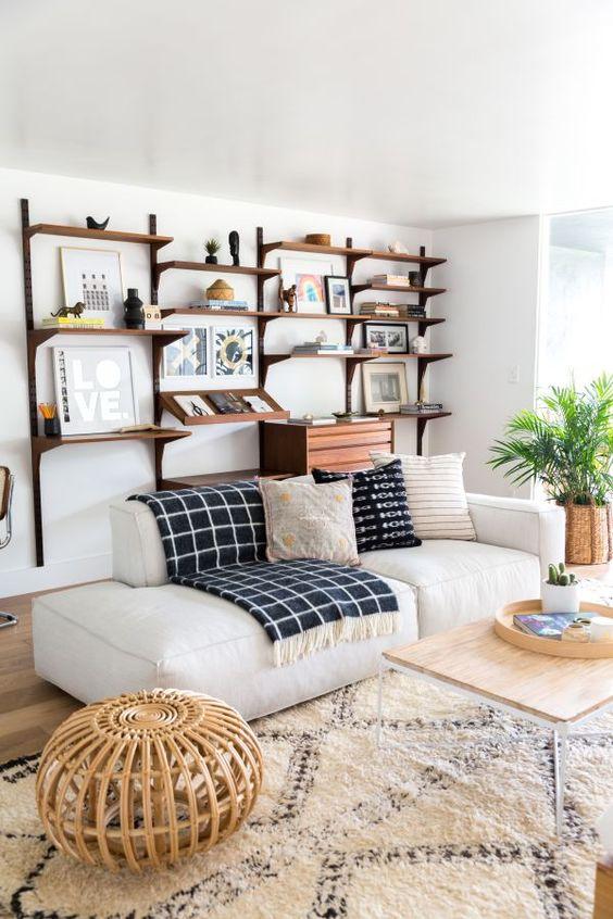un soggiorno moderno ed elegante con un mobile contenitore grande ma arioso sul muro, un divano basso bianco, uno sgabello in rattan e un tavolo