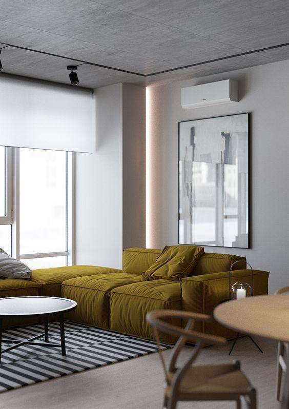 un soggiorno contemporaneo con un divano basso color senape, un tavolino basso, un'opera d'arte di grandi dimensioni e un tavolo rotondo e sedie