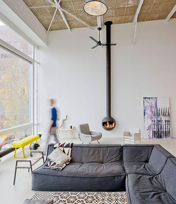 un soggiorno contemporaneo con una parete vetrata, un divano basso grigio, un focolare sospeso, alcuni bei mobili è molto bello
