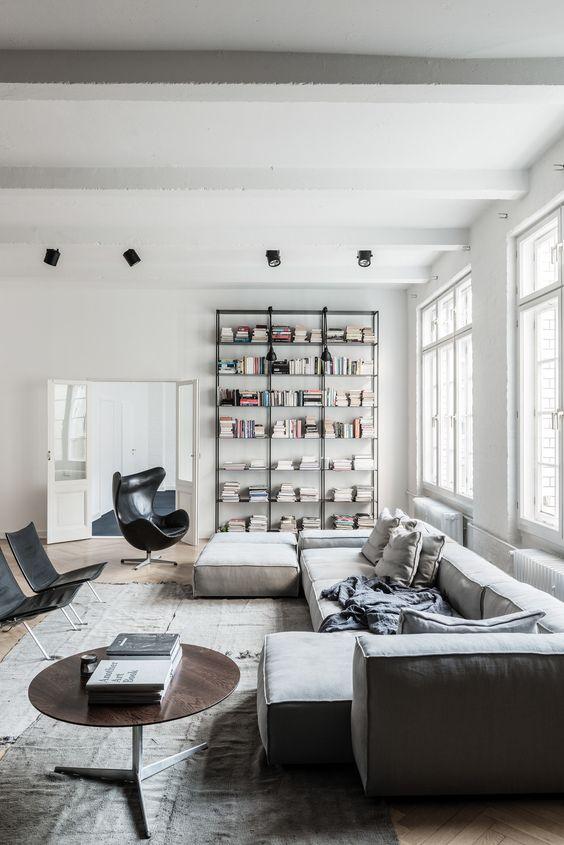 un soggiorno contemporaneo con un grande divano grigio, un tavolo rotondo, alcune sedie nere e un grande contenitore attaccato al muro