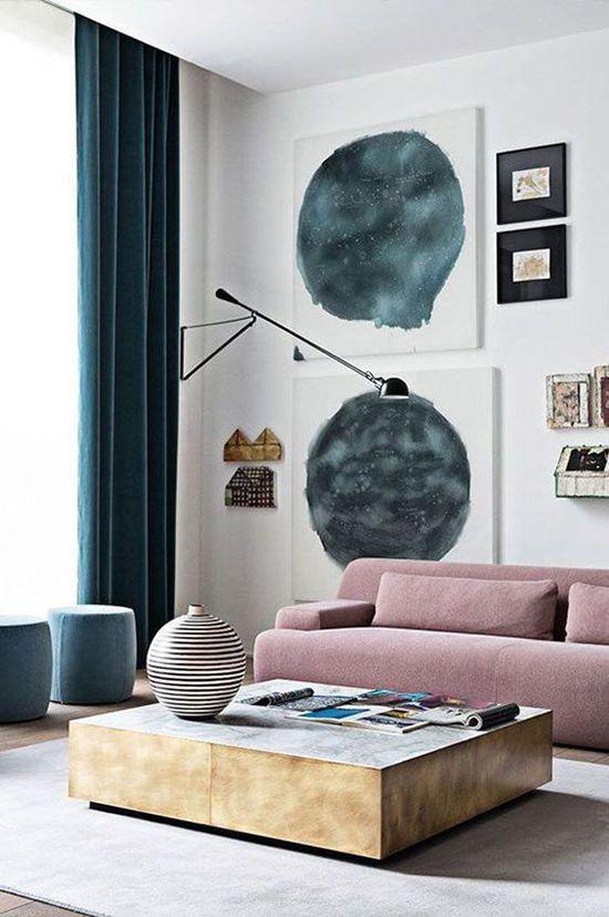 un soggiorno contemporaneo con un divano basso color malva, una galleria a parete, un tavolo basso in legno, tende verde acqua e pouf azzurri