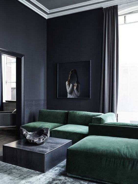 un soggiorno lunatico con pareti nere, un divano basso color smeraldo, un tavolino basso in metallo e un'opera d'arte