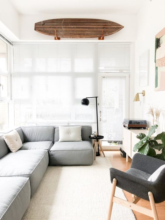 un soggiorno moderno con un divano basso grigio, una sedia grigia, una credenza neutra, una pianta in vaso e alcuni arredi e un'opera d'arte