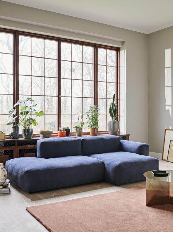 un soggiorno moderno con un divano blu basso, un tavolo metallico, un tappeto ruggine e un'intera collezione di piante in vaso sul davanzale della finestra