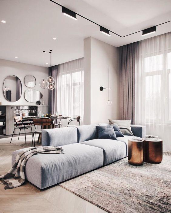 un lussuoso spazio contemporaneo con un divano basso azzurro, sgabelli metallici o tavolini e tocchi di rosa polvere