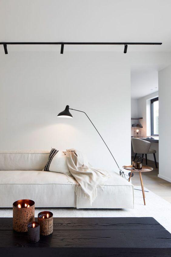 un soggiorno minimalista con un divano basso bianco, un tavolo nero, luci e un piccolo tavolo rotondo e candele sul tavolo