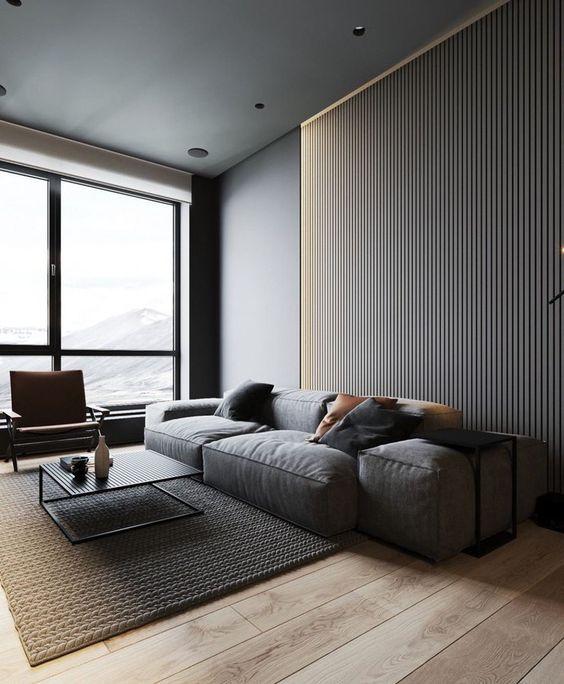 un soggiorno minimalista con una parete in lastre, un divano basso grigio, una sedia in pelle e un tavolino basso in metallo
