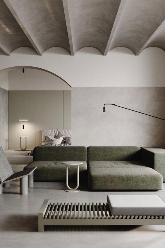 un soggiorno minimalista con un soffitto grigio, un divano basso verde, un divano letto, alcune sedie e lampade laconiche