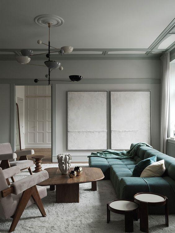 un raffinato soggiorno moderno con un divano verde basso, sedie color crema, diversi tavoli e un lampadario molto accattivante