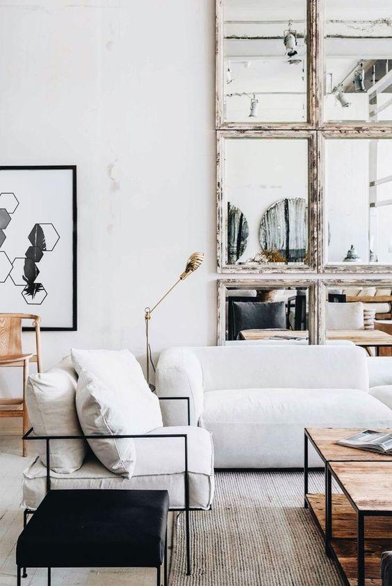 un grazioso soggiorno con un divano basso bianco, un tavolo basso in legno, uno sgabello nero, una parete con cornice a specchio e una bella opera d'arte
