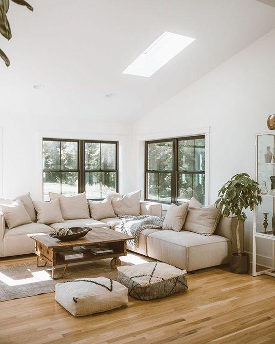 un rilassante soggiorno neutro con un divano basso neutro, un tavolino da caffè pallet, pouf, piante in vaso e molta luce naturale