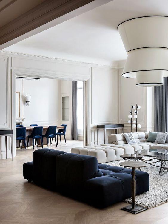 un raffinato soggiorno moderno con un divano basso color crema e blu scuro, lampade di tendenza e piccoli tavolini rotondi