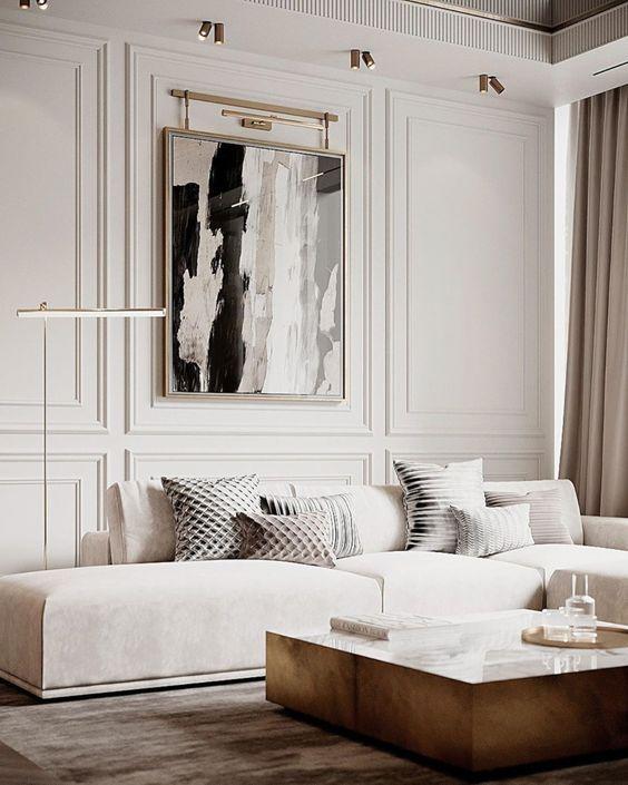 un raffinato soggiorno contemporaneo con un divano basso color crema, un tavolo basso, un'opera d'arte e alcune lampade e luci