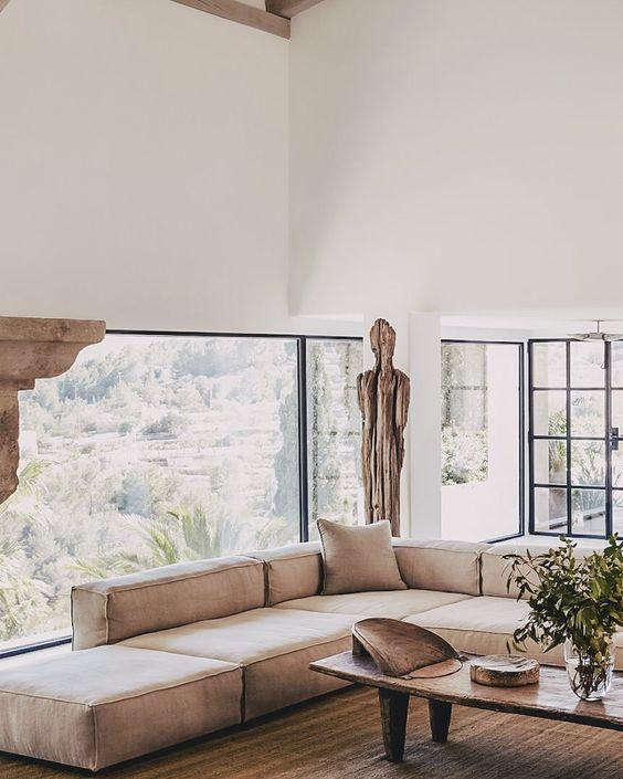 un soggiorno neutro e sereno con una parete vetrata, un divano basso marrone chiaro, tocchi di legno, un tavolino basso wabi-sabi e vegetazione
