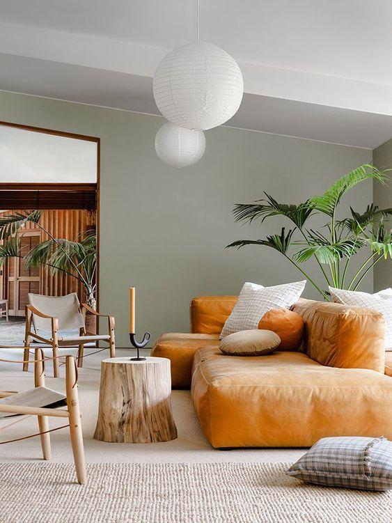 un grazioso soggiorno con pareti verdi, un divano basso color ambra, un albero sutmp, belle sedie e piante in vaso