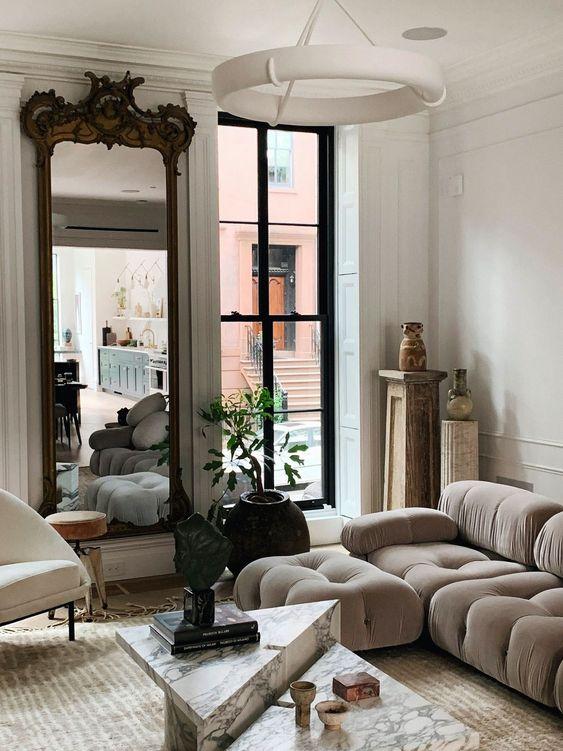 un soggiorno sofisticato con un divano basso grigio, tavoli in marmo, un grande specchio in una cornice raffinata e una pianta in vaso
