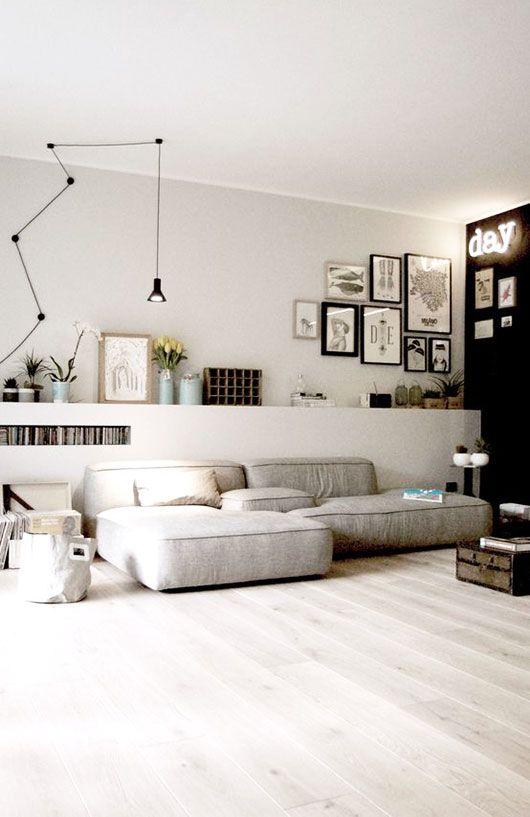 un elegante soggiorno contemporaneo con un muro di accento nero, un divano grigio basso, una mensola rialzata con piante in vaso e una galleria a parete
