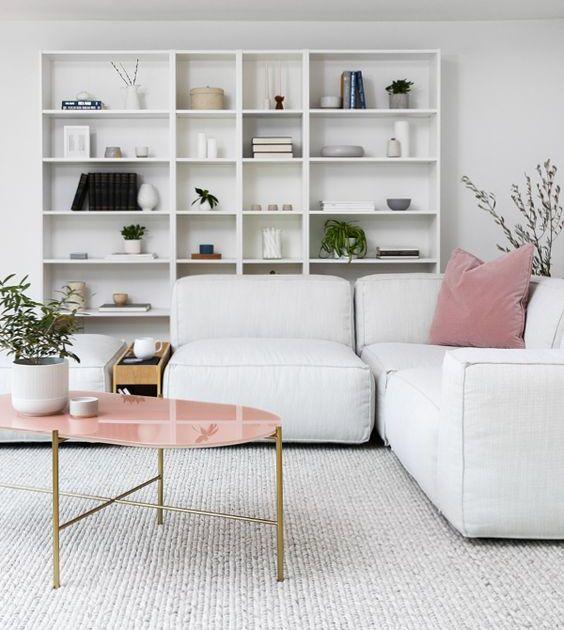 un soggiorno scandinavo con un contenitore aperto, un divano basso bianco, un tavolino rosa e cuscini rosa