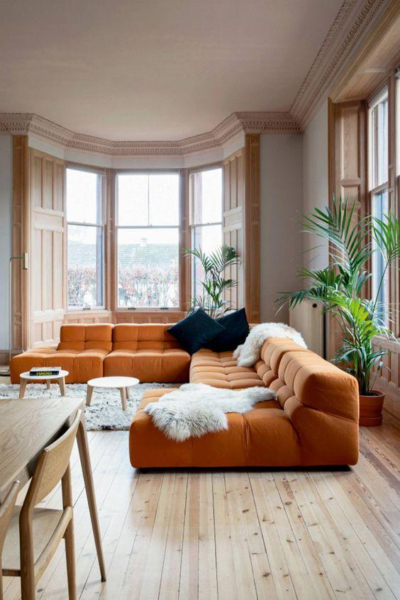un ampio soggiorno con un divano basso arancione, pelliccia sintetica, cuscini blu scuro e splendide finestre macchiate di luce