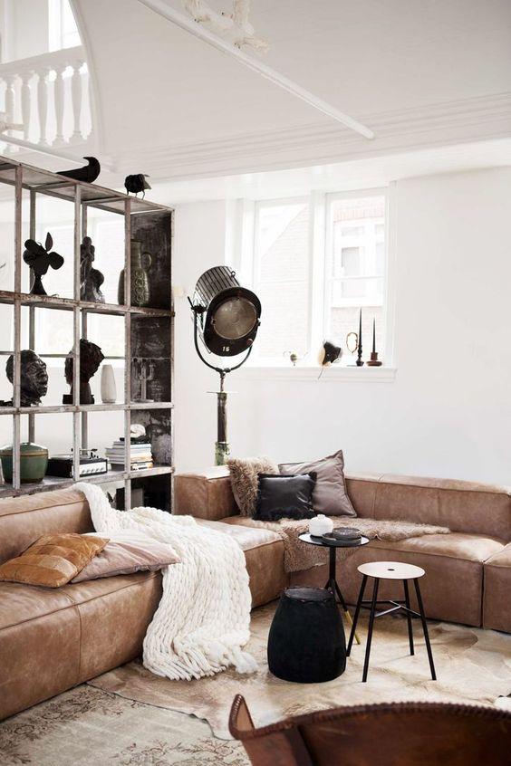 un elegante soggiorno con un divano basso marrone, piccoli tavolini, un grande contenitore e alcune lampade