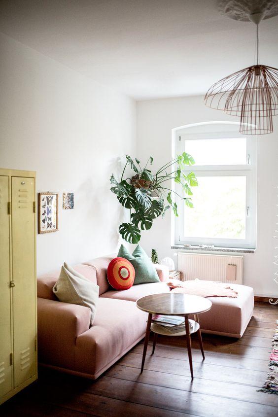 un piccolo soggiorno luminoso con un armadietto giallo, un divano rosa basso, alcune piante in vaso e una lampada a sospensione accattivante