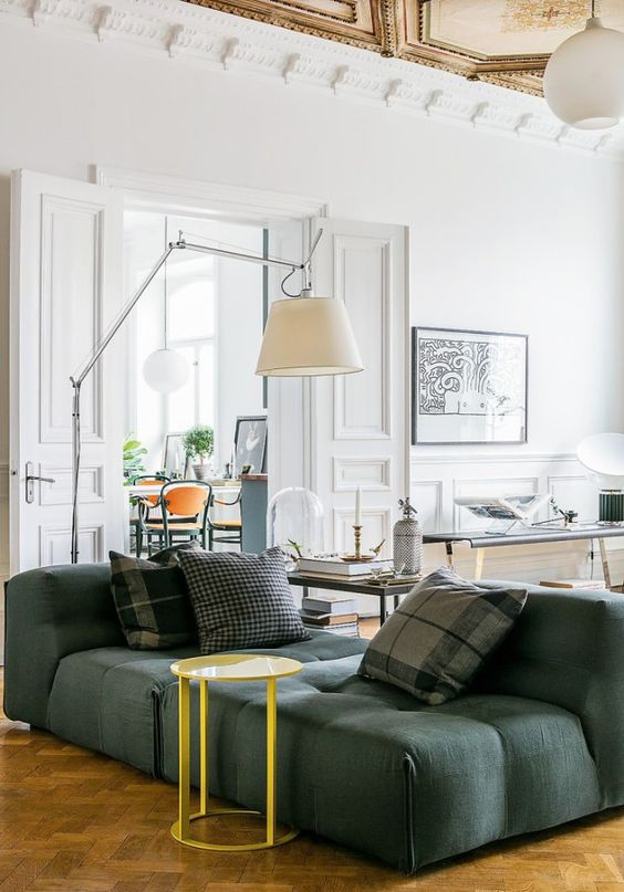 un soggiorno sofisticato con un divano verde basso, un tavolo giallo, lampade fresche e vari tavolini da caffè e un'opera d'arte