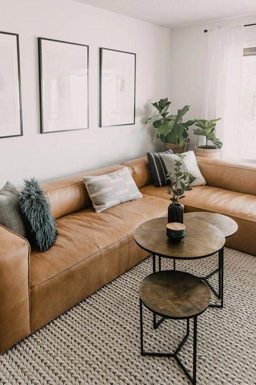 un elegante soggiorno moderno con un divano basso in pelle marrone, diversi tavoli rotondi, una galleria a muro e piante in vaso