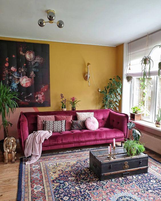 un soggiorno moderno chic con un muro accento senape, un divano rosa, un tappeto stampato boho, una valigia vintage e piante in vaso
