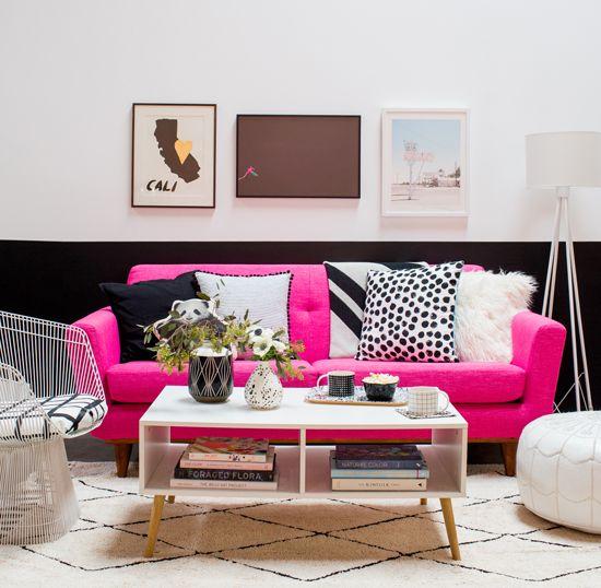 una camera da letto moderna ed elegante con una parete a blocchi di colore, un divano rosa caldo, un tavolino da caffè e una bella galleria a parete