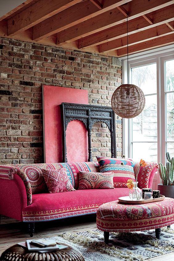 un soggiorno boho con un muro di mattoni, un divano rosa con cuscini stampati, un ottomano abbinato, una lampada a sospensione in rattan e un tappeto marocchino