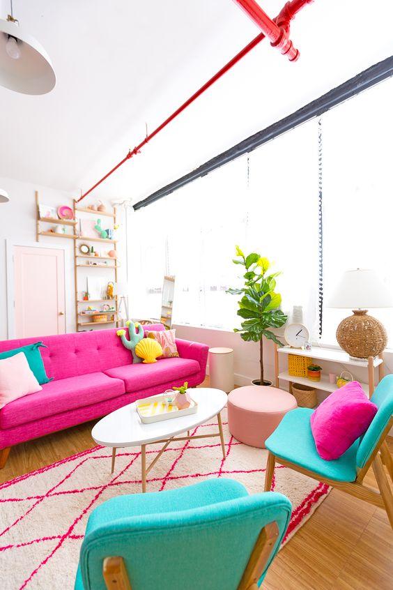 un allegro soggiorno con un divano rosa caldo, sedie turchesi con cuscini stravaganti, un tappeto stampato, una pianta in vaso e un pouf fard