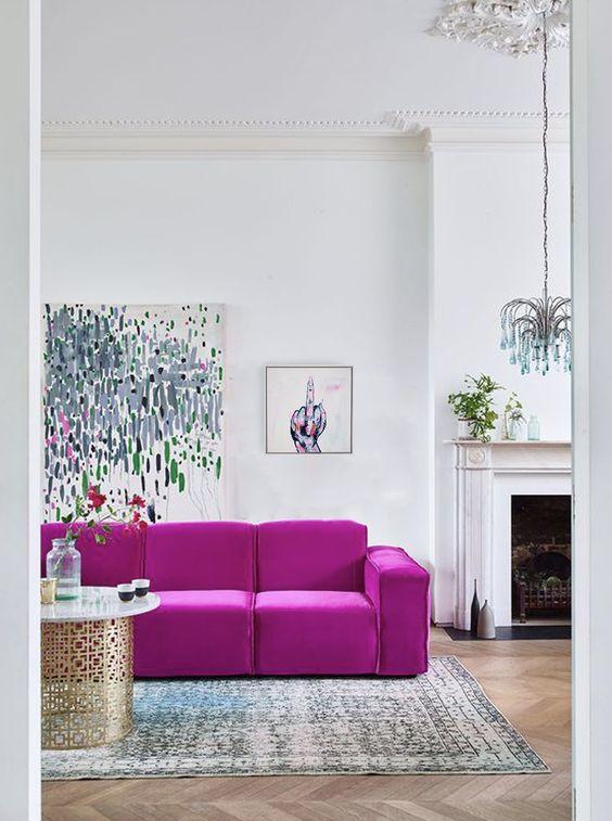 un soggiorno contemporaneo con camino, divano rosa caldo, opere d'arte fantastiche, un lampadario eccentrico, un tappeto stampato e un tavolo chic