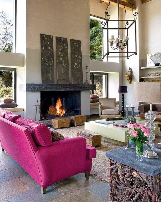 un soggiorno moderno con camino, un divano rosa caldo, opere d'arte floreali, un tavolo creativo con legno, ceppi d'albero e lampade accattivanti